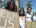 Bild von Aktion Deutschland Hilft 5 Kinder mit einem Schild auf dem Help Us und We Need Food Water steht