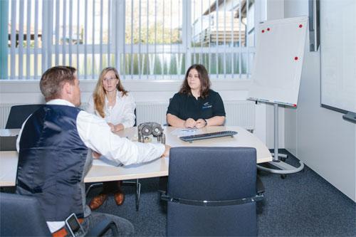 Drei Mitarbeiter von HERZOG INTERTEC am Konferenztisch bei Projektplanung