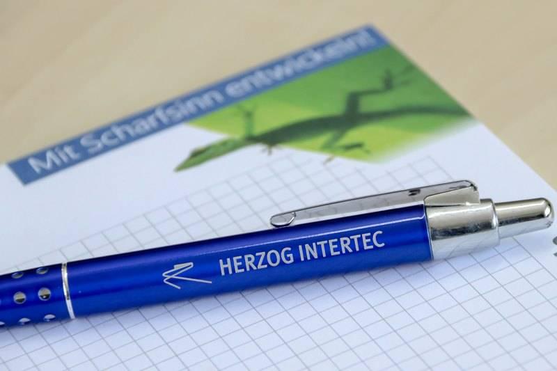 HERZOG INTERTEC Kugelschreiber und Schreibpapier auf einem Tisch